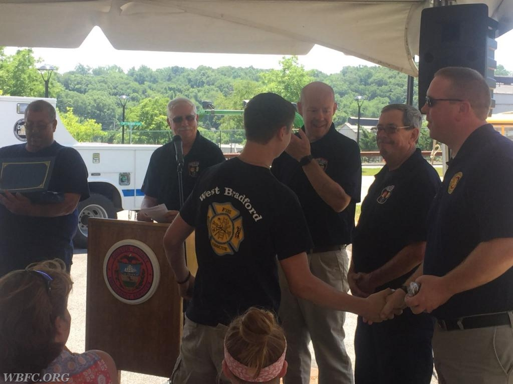 Sam receiving a handshake and a Challenge Coin from Chester County Fire Chiefs Assoc President Neil Vaughn